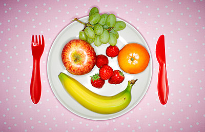 Plate with fruits building funny face and red plastic cutlery on pink cloth - p300m1028658f by Kai Schwabe