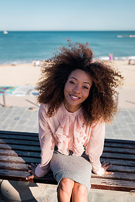 Portrait of smiling beautiful young woman with afro hairdo sitting on a bench at the beach - p300m2012877 von Mauro Grigollo