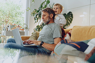 Playful boy leaning on father using laptop at home - p300m2266684 by Mareen Fischinger