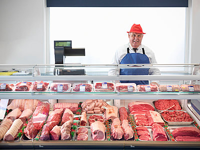 Butcher standing behind meat counter - p42914664f by Monty Rakusen