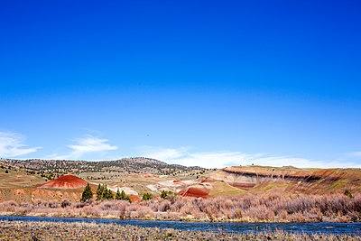 Creek near hills in desert landscape under blue sky, Painted Hills, Oregon, United States - p555m1412150 by Adam Hester