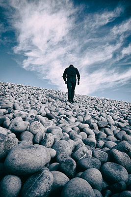 Rearview man walking up steep pebble beach - p597m1488676 by Tim Robinson