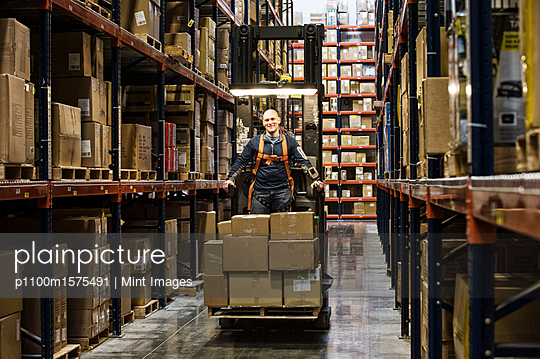 Warehouse worker wearing a safety harness while operating a motorized stock picker in an aisle between large racks of cardboard boxes holding product on pallets in a large distribution warehouse. - p1100m1575491 by Mint Images