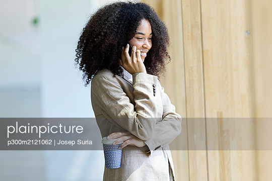 Smiling young businesswoman talking on the phone - p300m2121062 by Josep Suria