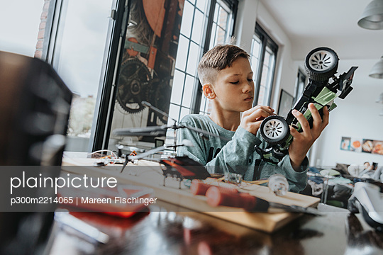Boy assembling on remote-controlled toy car with screwdriver - p300m2214065 by Mareen Fischinger