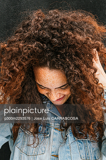 Smiling young woman with hand in curly brown hair - p300m2293576 by Jose Luis CARRASCOSA