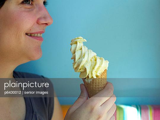 Junge Frau mit einem Softeis in einer Waffel  - p6430012 von senior images