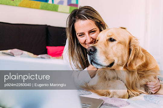 Italy, Young woman with dog on bed looking at laptop - p924m2283040 by Eugenio Marongiu