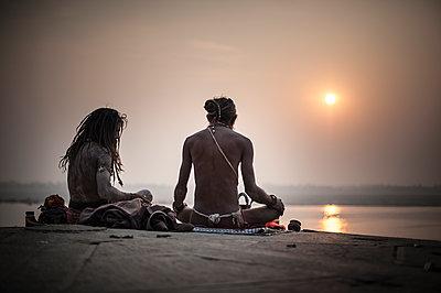 Two Sadhu praying at sunrise - p1007m1144423 by Tilby Vattard