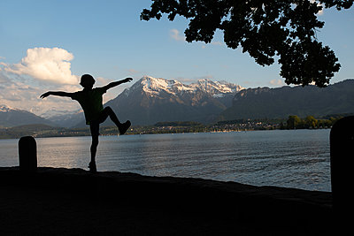 Silhouette of a joyful jumping child - p1354m2280259 by Kaiser