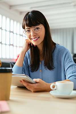 Portrait of smiling young woman with tepad at desk in office - p300m1587425 by Bonninstudio
