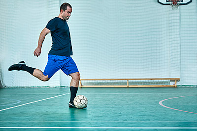 Man playing indoor soccer shooting the ball - p300m1587739 by Zeljko Dangubic