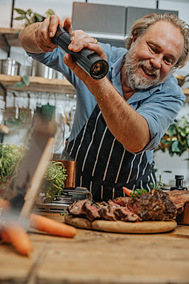 Smiling chef seasoning pepper on grilled tomahawk steak while standing in kitchen - p300m2256812 by Mareen Fischinger