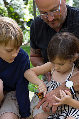 Father with son and daughter looking at monarch butterfly - p924m1157707 by Kinzie Riehm