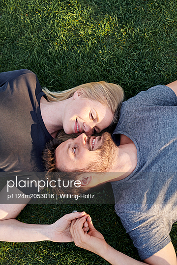 Happy couple relaxes in the meadow - p1124m2053016 by Willing-Holtz