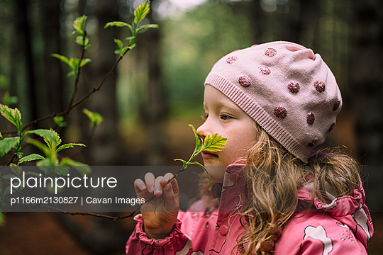 Adorable girl smelling branch in forest - p1166m2130827 by Cavan Images