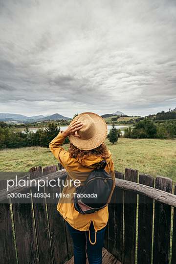 Young woman wearing yellow coat and backpack with a hand holding a hat in her head looking the lake landscape on top of a wood balcony - p300m2140934 by Mikel Taboada