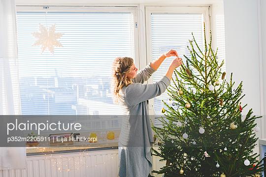 Finland, Helsinki, Woman decorating christmas tree - p352m2205911 by Eija Huhtikorpi