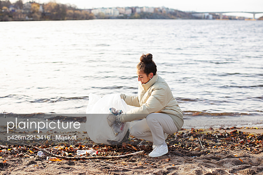 Young female environmentalist collecting waste while crouching by lake - p426m2213416 by Maskot