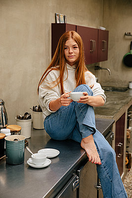 Red-haired girl has a cup of coffee in the kitchen - p1640m2242122 by Holly & John