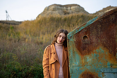 Young woman leaning against rusty container - p1646m2232032 by Slava Chistyakov