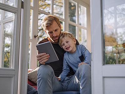 Father and son using tablet in sunroom at home - p300m2167217 by Kniel Synnatzschke
