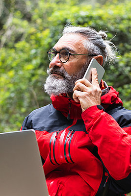 Senior man with laptop on phone call in forest during weekend - p300m2277358 by NOVELLIMAGE