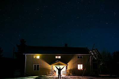 Person in front of illuminated house at night - p312m2079949 by Matilda Holmqvist