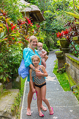 Caucasian family smiling on tropical path - p555m1419360 by Marc Romanelli
