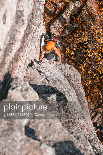 Woman climbing in the fall in the Gunks - p1166m2113010 by Cavan Images