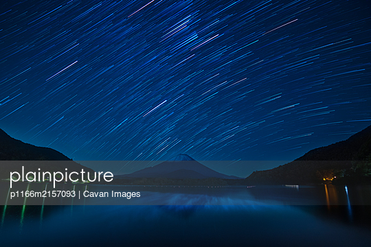 Star trails over Mount Fuji on a clear night from lake Shoji, Yamanashi Prefecture, Japan - p1166m2157093 by Cavan Images