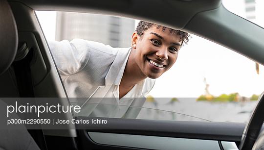 Smiling female professional looking through car window - p300m2290550 by Jose Carlos Ichiro