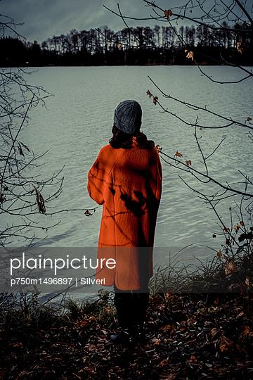 Frau blickt auf einen See in der Dämmerung - p750m1496897 von Silveri