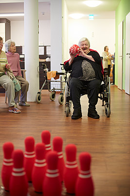 Age demented senior woman bowling with foam ball in a nursing home - p300m2219176 by Heinz Linke