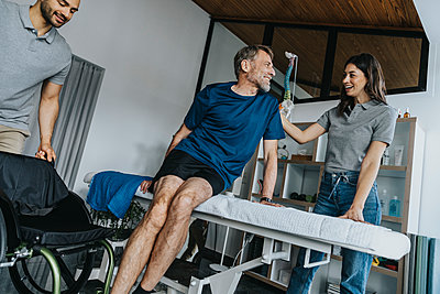 Smiling female physical therapist consoling mature male patient at massage table in practice - p300m2276803 by Mareen Fischinger