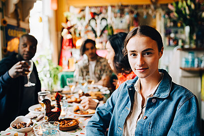 Portrait of confident young woman sitting against friends at table in restaurant during dinner party - p426m2046323 by Maskot