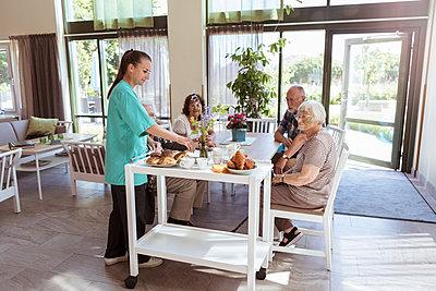 Female caretaker serving breakfast to senior people in nursing home - p426m2072569 by Kentaroo Tryman
