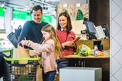 Smiling parents looking at daughter arranging paper bags in shopping cart - p426m2097448 by Maskot