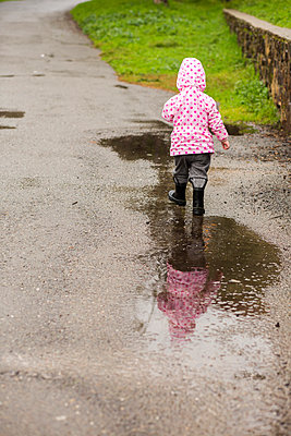 Caucasian girl wearing boots walking in puddle - p555m1482100 by Adam Hester