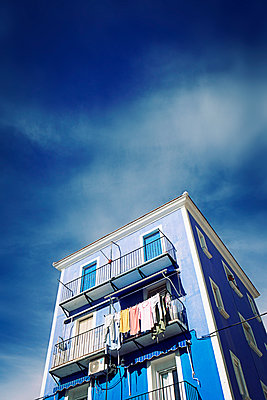 Blue house with washing hanging from balcony - p597m2142986 by Tim Robinson