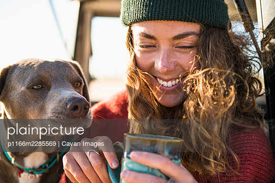 Young woman enjoying cup of coffee in the morning beach car camping - p1166m2285569 by Cavan Images