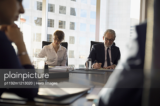 Lawyers taking notes in conference room meeting