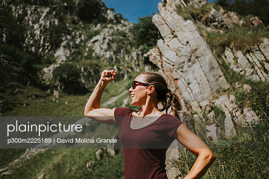 Smiling woman flexing muscles while standing against rock formation on sunny day - p300m2225189 by David Molina Grande