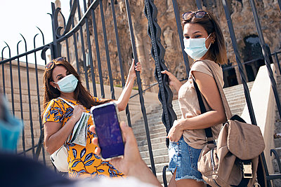 Man taking photo of women wearing face mask standing by gate against Sagrada Familia at Barcelona, Catalonia, Spain - p300m2240855 by Josep Suria