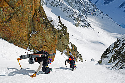Europe, France, French Alps, Haute Savoie, Chamonix, skier carrying sis uphill in the Col du Passon off piste ski touring area MR - p652m716730 by Christian Kober