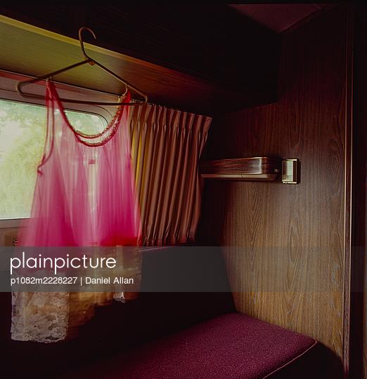 Pink underwear on clothes hanger in a caravan - p1082m2228227 by Daniel Allan