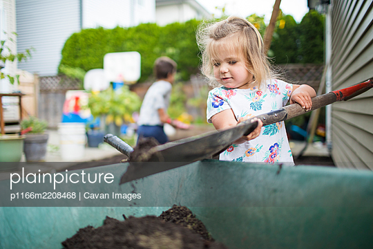 Cute girl shoveling dirt into wheelbarrow in backyard. - p1166m2208468 by Cavan Images