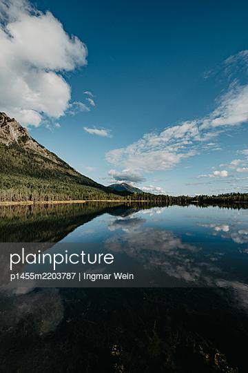 Wolken spiegeln sich in einem Bergsee - p1455m2203787 von Ingmar Wein