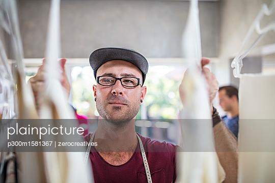 Fashion designer looking at stock in studio - p300m1581367 von zerocreatives