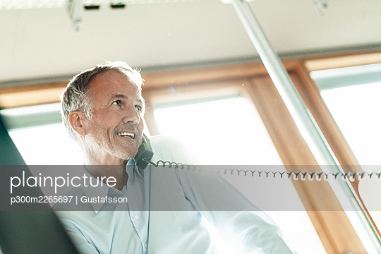 Smiling businessman looking away while talking on telephone in office - p300m2265697 by Gustafsson